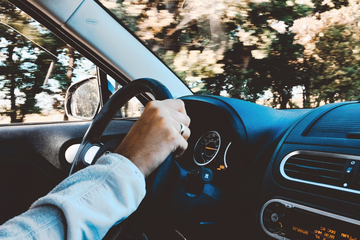 Hand holding steering wheel in car.