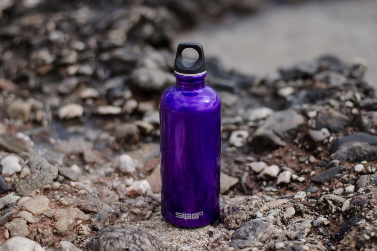 A purple water bottle on some rocks.