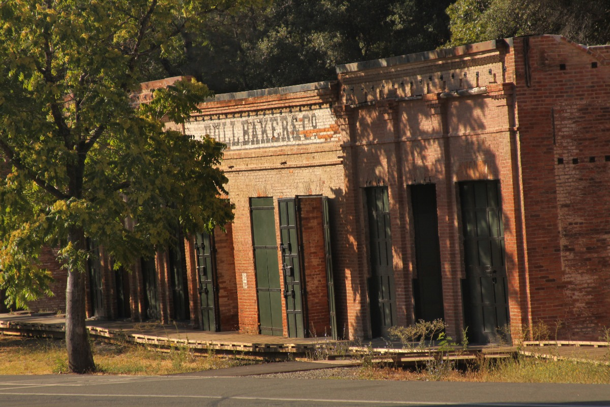 Brick buildings with green doors at Shasta State Historic Park.