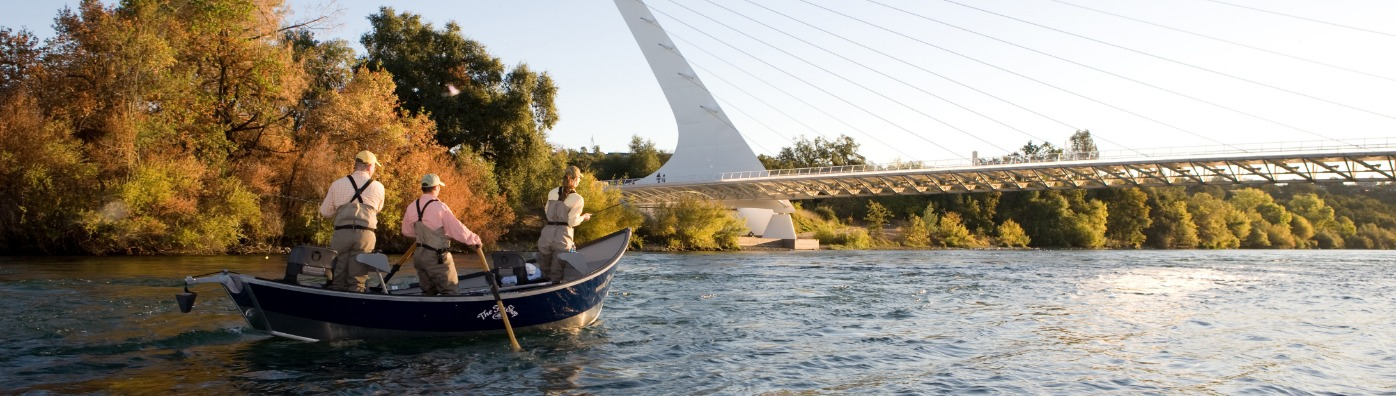 A group of people fishing on the Sacramento River beneath the Sundial Bridge in Redding, CA.