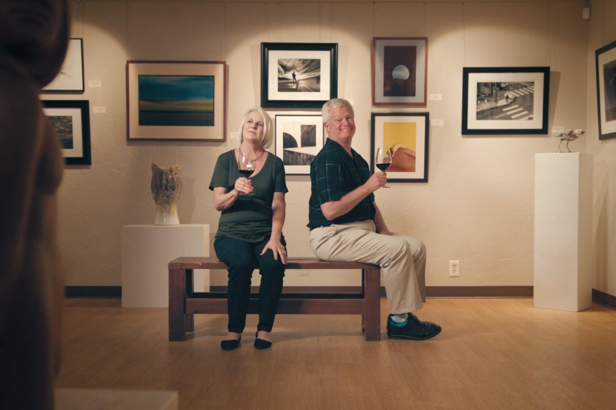 A man and a woman having wine in the Carter House Art Gallery.
