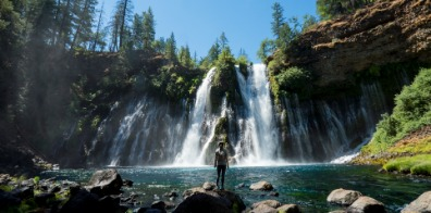 Woman standing at the base of a waterfall at McArthur-Burney Falls Memorial State Park.