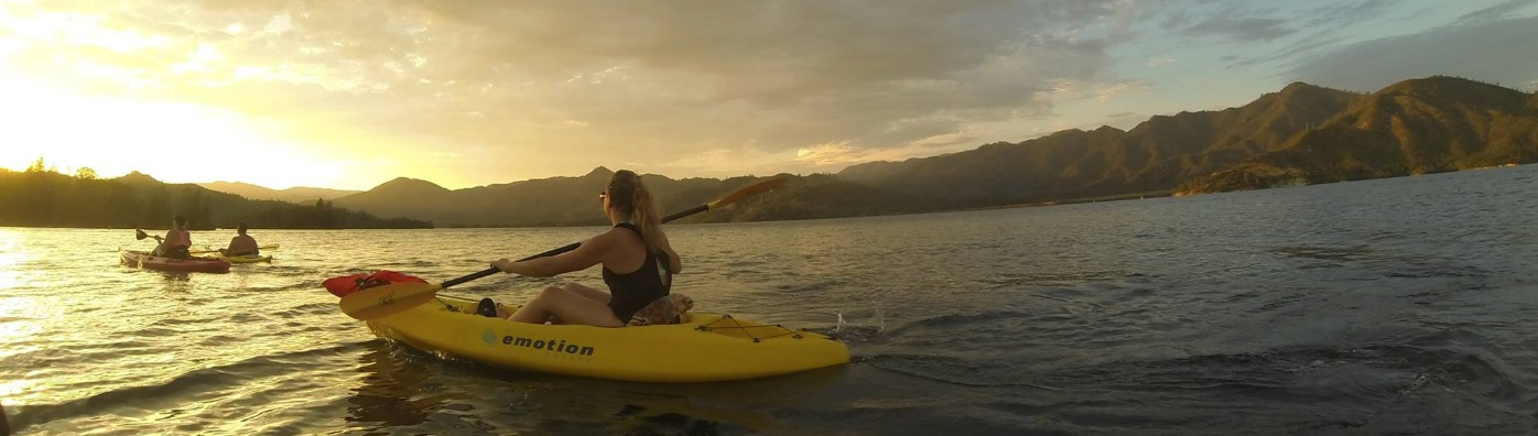 Woman kayaking at Whiskeytown National Recreation Area at sunset.