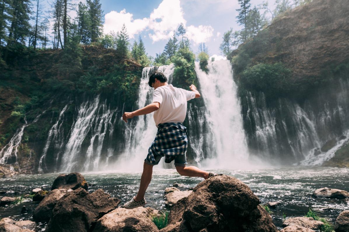 Man jumping across rocks at McArthur-Burney Falls Memorial State Park.