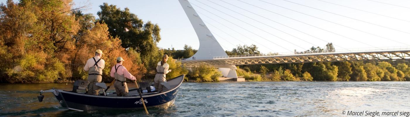 Three people in a boat fishing beneath the Sundial Bridge in Redding, CA.